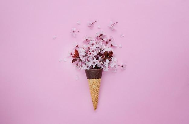 Вишневый цвет в рожке мороженого на розовом фоне