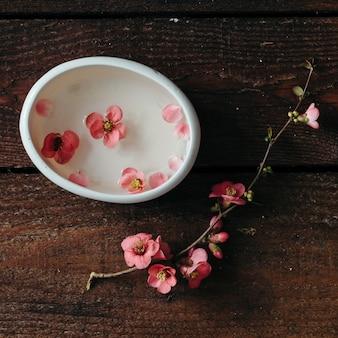 木製のテーブルの上の水ボウルと桜の小枝。フラットレイ。