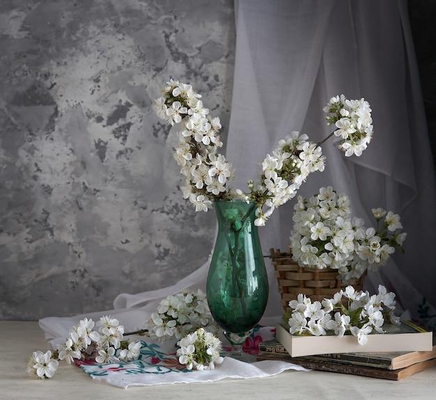 Вишневый цвет в стеклянной вазе на сером фоне. весенний натюрморт.
