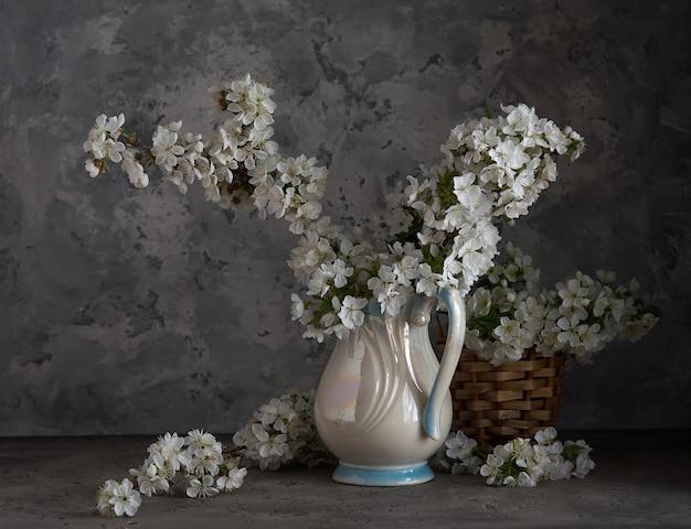회색 배경에 흰색 꽃병에 벚꽃입니다. 봄 정물.