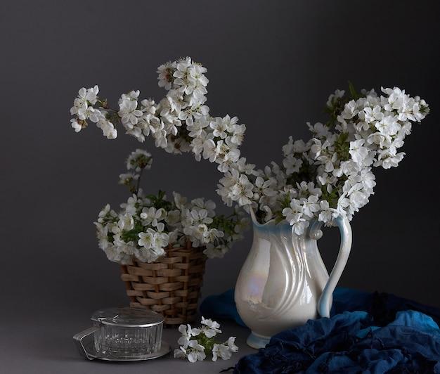회색 배경에 흰색 꽃병에 벚꽃
