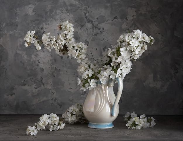 Вишневый цвет в белой вазе на сером фоне