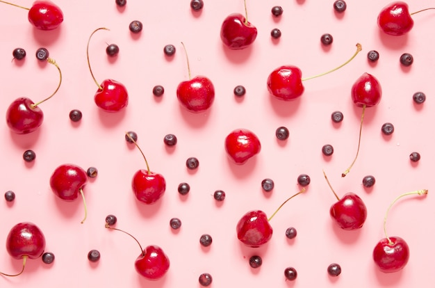 Cherry and blueberry pattern on pink background