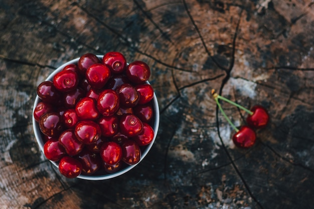 Cherry in bowl on wooden background
