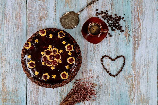 Cherry cake with chocolate glaze, cup of coffee and flowers