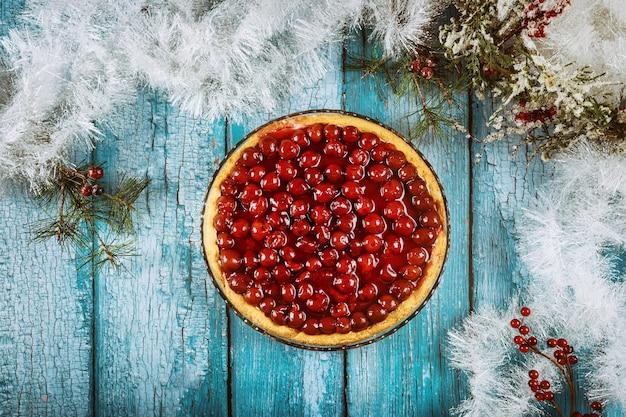 チェリーゼリーを上に載せたチェリーチーズケーキとケーキシャベル。クリスマスの装飾。