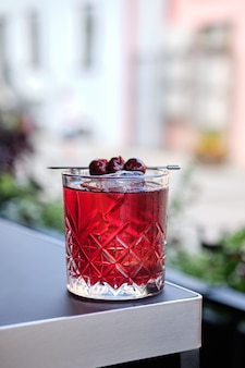 Cherry cocktail on the edge of the table on outdoor terrace (photo with shallow depth of field)