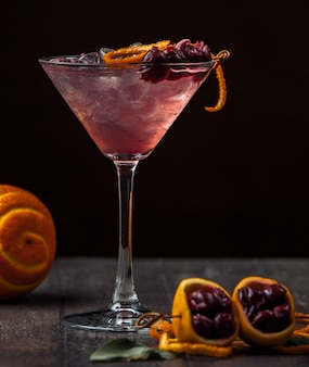 Cherry cocktail garnished with cherry and orange zest and ice