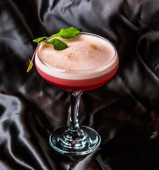 Cherry cocktail with white foam on a glass with mint leaves.