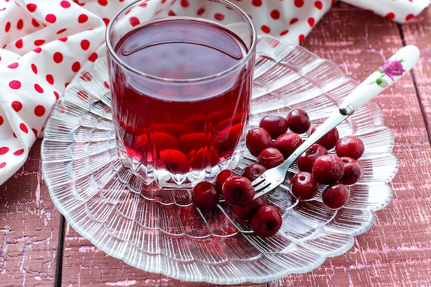 Cherry compote in a glass cherries and fork on a patterned transparent plates