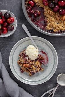 ダークグレーの表面に新鮮なベリー、ピーカンナッツ、バニラアイスクリームを添えたチェリークランブルパイ