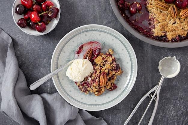 ダークストーンの背景に新鮮なベリー、ピーカンナッツ、バニラアイスクリームとチェリークランブルパイ。