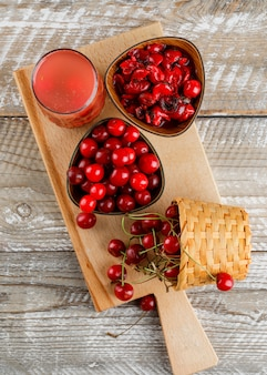 Cherry drink in a jug with cherries, jam on wooden and cutting board