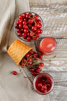 Вишневый напиток с вишней, вареньем в кувшине на деревянном и кухонном полотенце