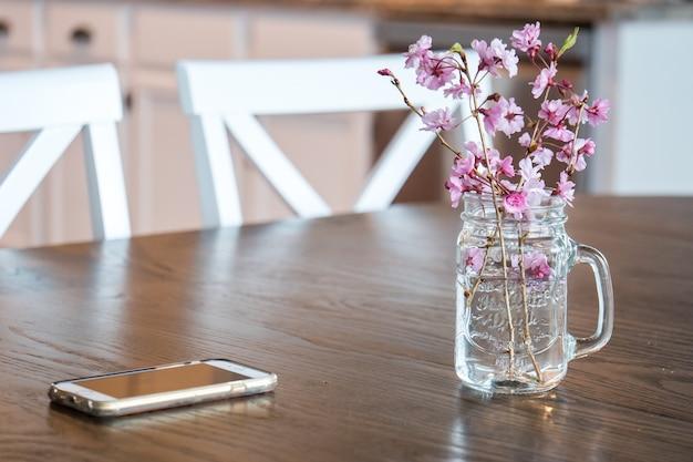 ライトの下のテーブルの上の水のガラスの桜の花と枝