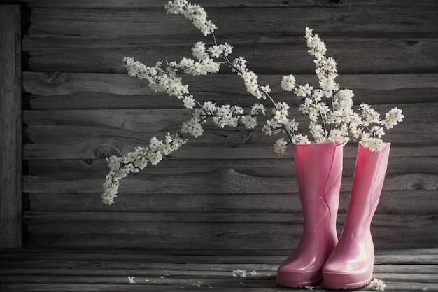 古い木製の背景にピンクの長靴の桜の花