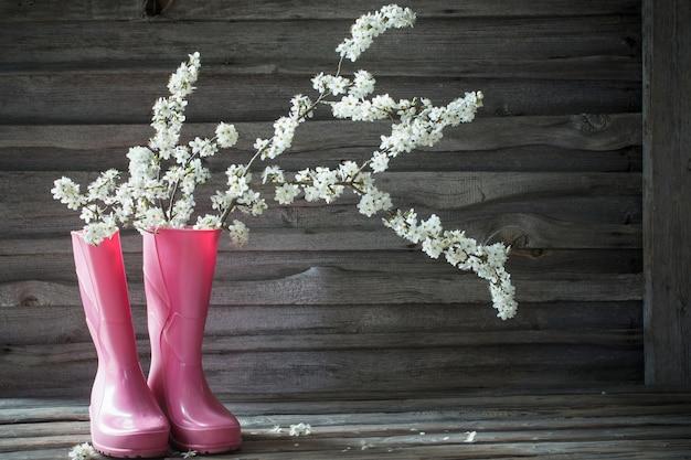 古い木の表面にピンクの長靴の桜の花