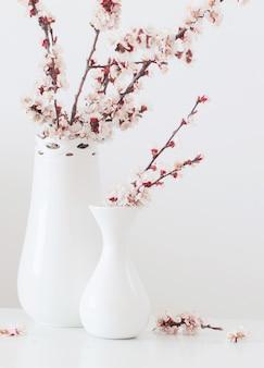 흰색 바탕에 분홍색 촛불 꽃병에 체리 꽃