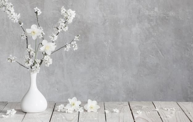 Вишневые цветы в белой вазе на фоне старой серой стены