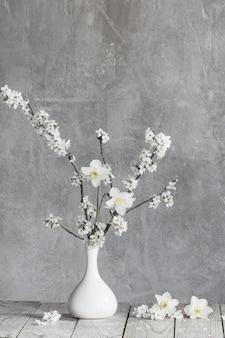 Вишневые цветы в белой вазе на поверхности старой серой стены