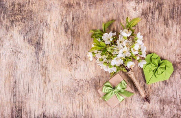 Cherry flowers, paper heart and gift box on wooden background
