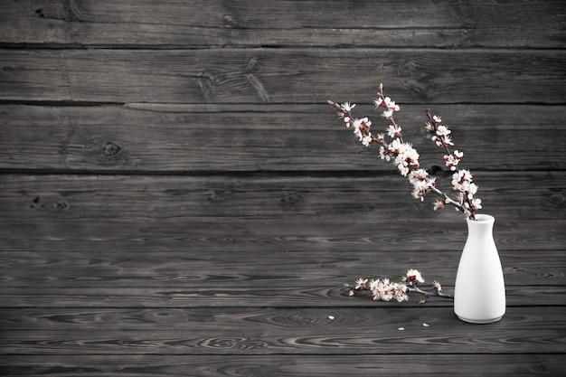 Cherry flowers in vase on dark wooden  background