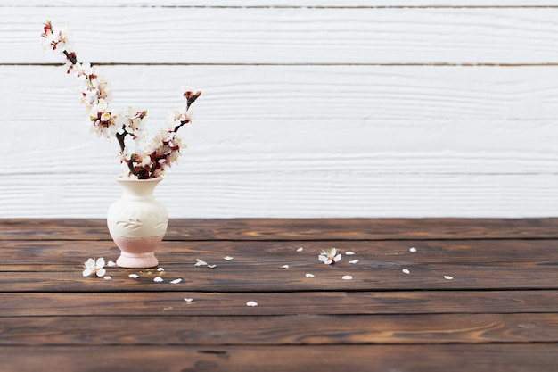 Cherry flowers in vase on wooden surface