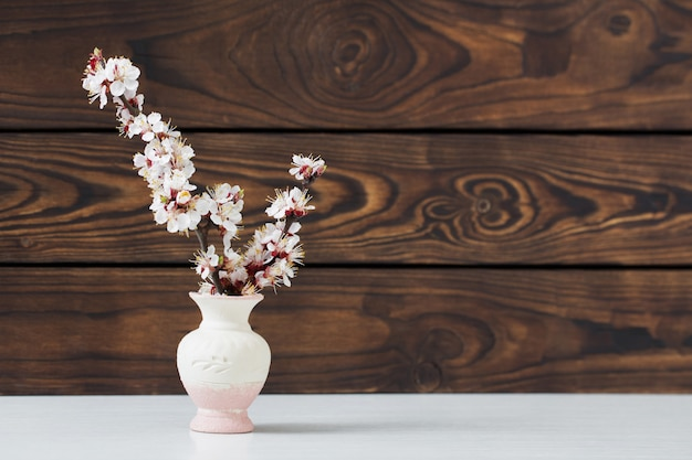Cherry flowers in vase on wooden table