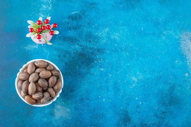 Cherry fruits in a vase next to pecan nuts in a bowl , on the blue table.