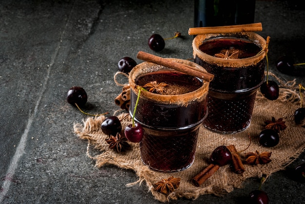Cherry hot sangria with cinnamon, anise, wine and spices on a stone dark and wooden background
