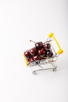 슈퍼마켓을 위한 미니어처(작은) 식료품 카트의 체리. 흰색 바탕에 열매와 장난감 카트입니다. 클로즈업, 텍스트 복사 공간, 위쪽 보기.