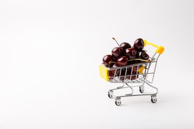 슈퍼마켓을 위한 미니어처(작은) 식료품 카트의 체리. 흰색 바탕에 열매와 장난감 카트입니다. 클로즈업, 텍스트를 위한 공간을 복사합니다.