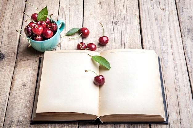 Вишня в красивой бирюзовой чашке и старой книге на деревянном столе. фрукты, образование