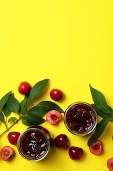 Вишневое варенье и ингредиенты на желтом фоне