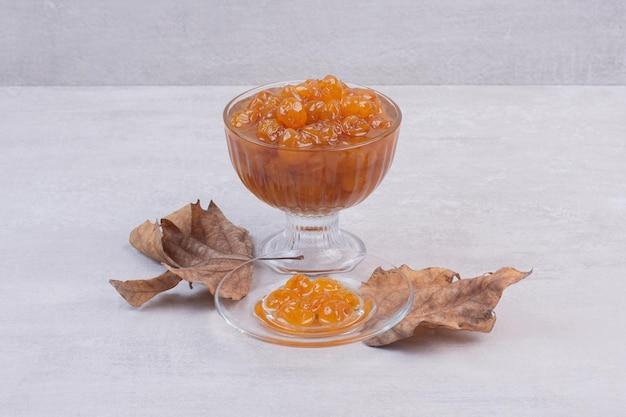 Marmellata di ciliegie in vetro e foglie secche sul tavolo bianco.
