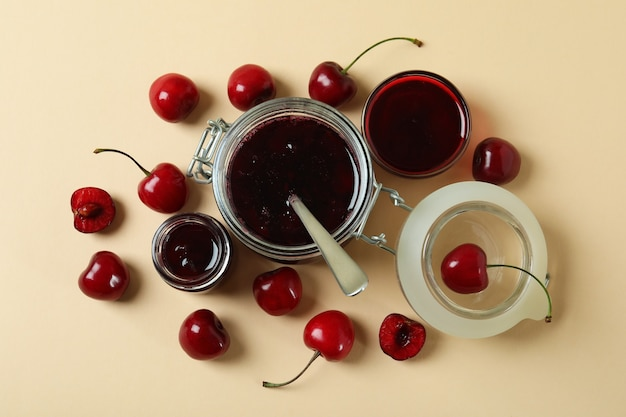 Cherry jam and ingredients on beige background