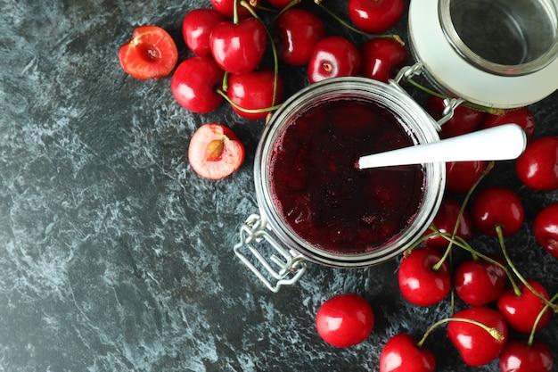 Cherry jam and ingredients on black smokey background