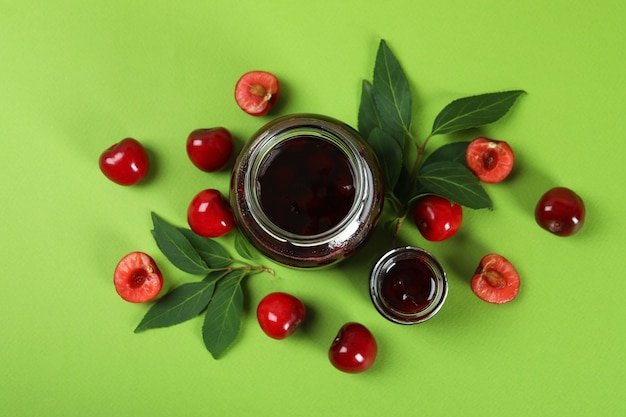 Cherry jam and ingredients on green background