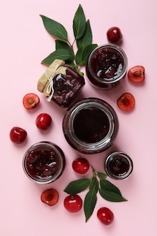 Cherry jam and ingredients on pink background
