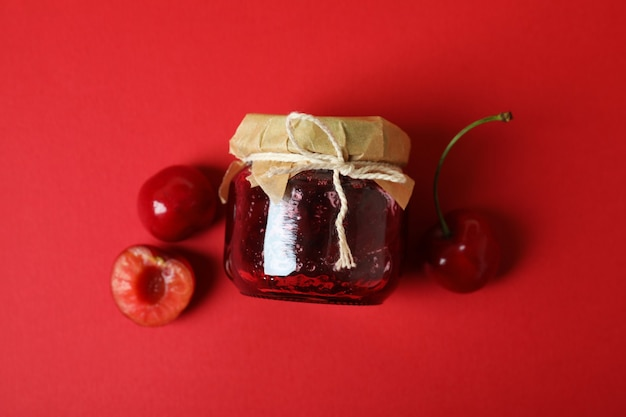 Cherry jam and ingredients on red background