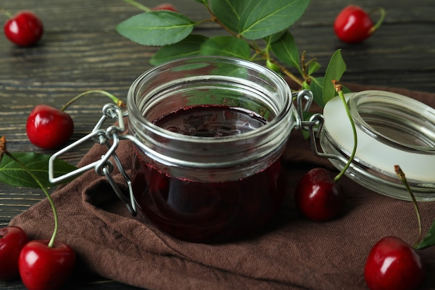 Cherry jam and ingredients on rustic wooden table