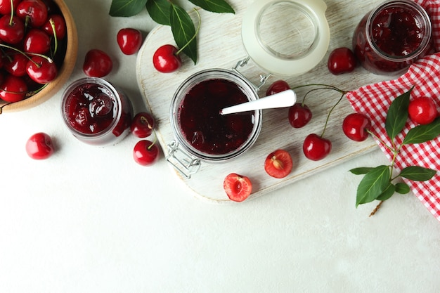 Cherry jam and ingredients on white textured table