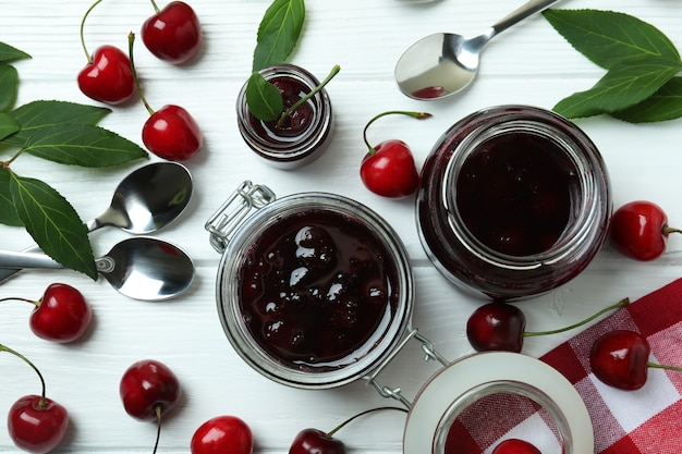 Cherry jam and ingredients on white wooden table