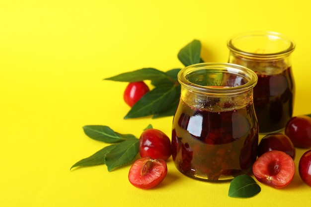 Cherry jam and ingredients on yellow background