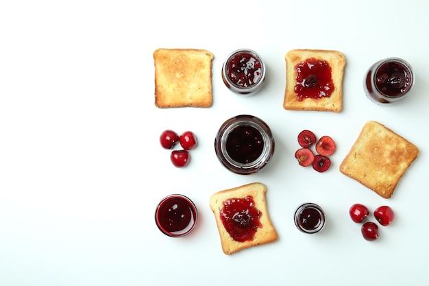 Бутерброды с вишневым джемом и ингредиенты на белом фоне