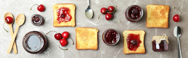 Cherry jam sandwiches and ingredients on gray textured background