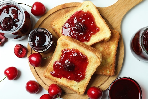 Cherry jam sandwiches and ingredients on white background