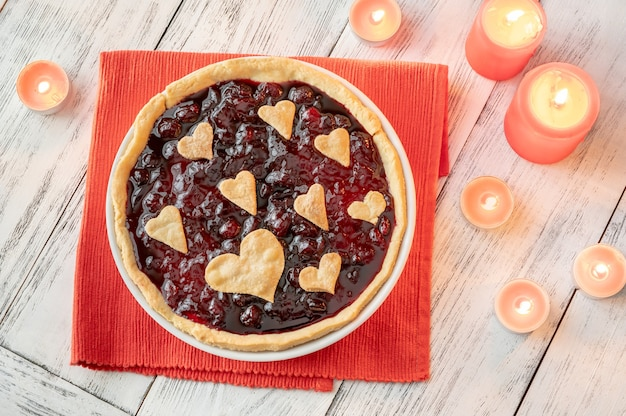 Cherry jam tart decorated with hearts, with burning candles