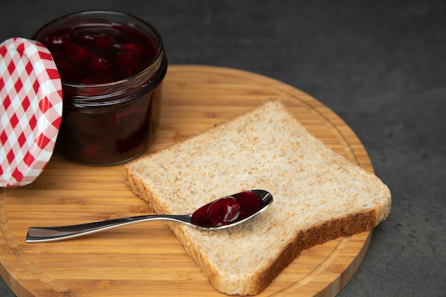 Cherry jam with berries in a glass jar with an open red and white lid next. next to a wholegrain toast with an empty teaspoon.