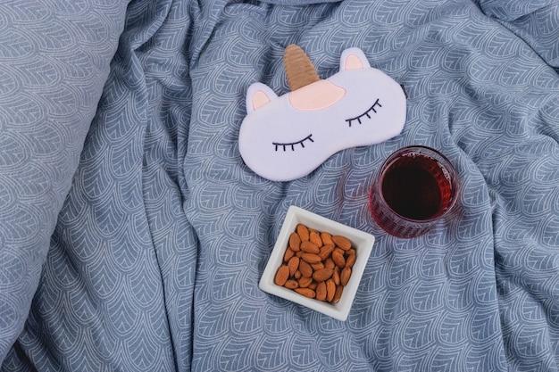 睡眠マスクの隣のベッドで健康的な睡眠のためのチェリージュースとアーモンド。
